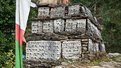 """Mani Stones along the Trail to Everest: Along the paths of regions under the influence of Tibetan Buddhism the traveler is often confronted with Mani walls. These stone structures are a compilation of intricately carved stone tablets, most with the inscription """"Om Mani Padme Hum"""" which loosely translates to """"Hail to the jewel in the lotus"""". These walls should be passed or circumvented from the left side, the clockwise direction in which the earth and the universe revolve, according to Buddhist doctrine."""