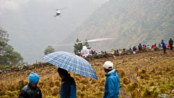 Helicopters arriving at Surke for 'The Evacuation': We had been stranded in Lukla for 4 days when we got the word that an evacuation had been arranged. We hiked rapidly for 90 minutes downhill to reach Surke from Lukla before the clouds closed in again.